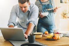 Les jeunes ménage dans la cuisine L'homme tient la table proche et utilise l'ordinateur portable, épouse enceinte se tient à côté Photos libres de droits