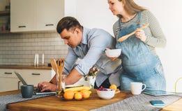 Les jeunes ménage dans la cuisine L'homme tient la table proche et utilise l'ordinateur portable, épouse enceinte se tient à côté Photos stock