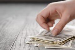 Les jeunes mains femelles comptent des billets d'un dollar sur le bois Image stock