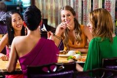 Les jeunes mangeant dans le restaurant de l'Asie Photos stock