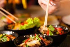 Les jeunes mangeant dans le restaurant thaï Photographie stock libre de droits