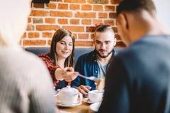 Les jeunes mangeant dans un restaurant Réunion du ` s d'ami Images libres de droits