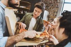 Les jeunes mangeant de la pizza Image stock