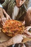Les jeunes mangeant de la pizza Photographie stock libre de droits