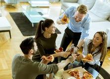 Les jeunes mangeant de la pizza et buvant du cidre dans l'intérieur moderne images libres de droits