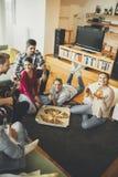 Les jeunes mangeant de la pizza et buvant du cidre dans la chambre Photos stock