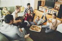 Les jeunes mangeant de la pizza et buvant du cidre dans la chambre Image stock
