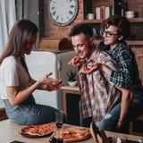 Les jeunes mangeant de la pizza et souriant à la partie Photo stock