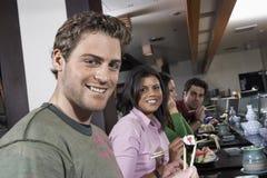Les jeunes mangeant des sushi avec des baguettes dans le restaurant Image libre de droits