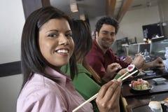 Les jeunes mangeant des sushi avec des baguettes dans le restaurant Images libres de droits