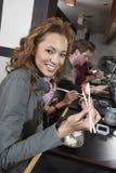 Les jeunes mangeant des sushi avec des baguettes dans le restaurant Photos stock