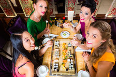 Les jeunes mangeant des sushi dans le restaurant Photo libre de droits