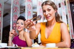Les jeunes mangeant des sushi dans le restaurant de l'Asie Photographie stock libre de droits