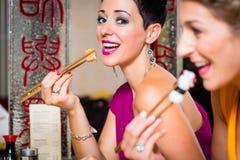 Les jeunes mangeant des sushi dans le restaurant de l'Asie Images stock