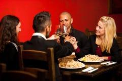 Les jeunes mangent le dîner de fruits de mer au restaurant et boivent du vin Photos stock