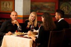 Les jeunes mangent le dîner de fruits de mer au restaurant et boivent du vin Photo libre de droits