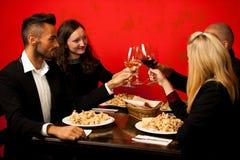 Les jeunes mangent le dîner de fruits de mer au restaurant et boivent du vin Image stock