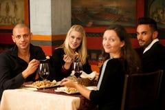 Les jeunes mangent le dîner de fruits de mer au restaurant et boivent du vin Image libre de droits