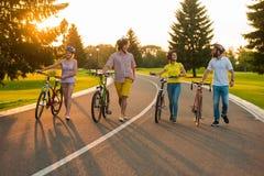 Les jeunes marchant avec des bicyclettes sur la route Photo libre de droits