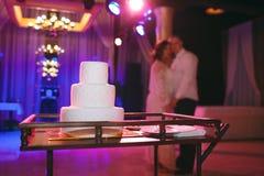 Les jeunes mariées avec du charme embrassant près du gâteau de mariage Image stock