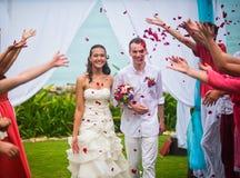 Les jeunes mariés après la cérémonie de mariage Les invités ont versé les nouveaux mariés avec des pétales de rose photographie stock libre de droits