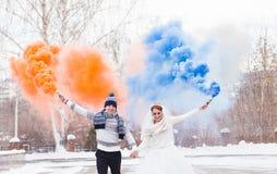 Les jeunes mariés avec des bombes fumigènes en hiver Image stock