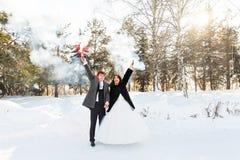Les jeunes mariés avec des bombes fumigènes en hiver Photo libre de droits