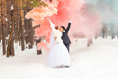 Les jeunes mariés avec des bombes fumigènes en hiver images libres de droits