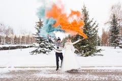 Les jeunes mariés avec des bombes fumigènes en hiver photographie stock