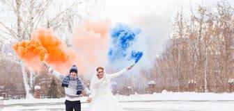 Les jeunes mariés avec des bombes fumigènes en hiver photos stock