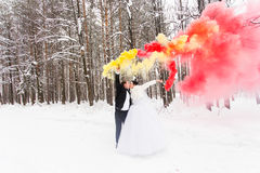 Les jeunes mariés avec des bombes fumigènes en hiver photographie stock libre de droits