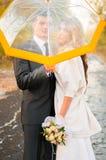 Les jeunes mariés cachés derrière le parapluie image libre de droits
