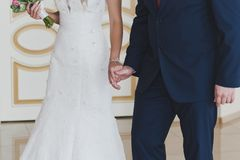Les jeunes mariés dans l'excitation saisissant des mains photo stock