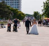 Les jeunes mariés dans la robe de mariage et le smoking marchent après un ajouter à deux enfants dans des poussettes sur le trott photos libres de droits