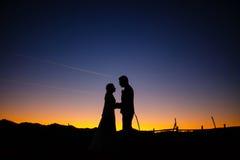 Les jeunes mariés dans le coucher du soleil avec l'avion traînent à l'arrière-plan Photographie stock