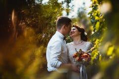 Les jeunes mariés dans le feuillage des arbres photos stock