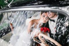 Les jeunes mariés derrière la roue de la rétro voiture mariage Image stock