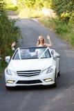 Les jeunes mariés Driving Away In ont décoré la voiture photographie stock libre de droits