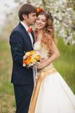 Les jeunes mariés en parc luxuriant au printemps Images libres de droits