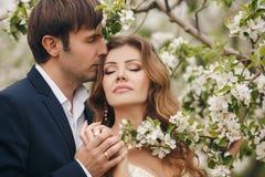 Les jeunes mariés en parc luxuriant au printemps Photos libres de droits