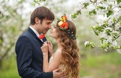 Les jeunes mariés en parc luxuriant au printemps Images stock