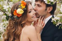 Les jeunes mariés en parc luxuriant au printemps Photographie stock