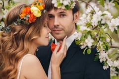 Les jeunes mariés en parc luxuriant au printemps Photographie stock libre de droits