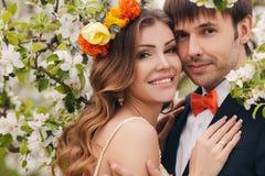 Les jeunes mariés en parc luxuriant au printemps Photo libre de droits
