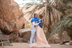Les jeunes mariés enveloppés dans le drapeau de l'Ukraine embrassent en canyon Photo stock