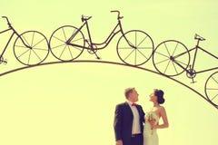 Les jeunes mariés et un fer arquent sous une forme de bicyclette Images stock