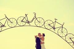 Les jeunes mariés et un fer arquent sous une forme de bicyclette Image stock