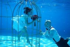 Les jeunes mariés et une eau sous-marine de piscine de cage à oiseaux plongent Photos stock