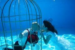 Les jeunes mariés et une eau sous-marine de piscine de cage à oiseaux plongent Images stock