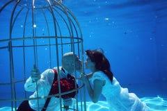 Les jeunes mariés et une eau sous-marine de piscine de cage à oiseaux plongent Image libre de droits